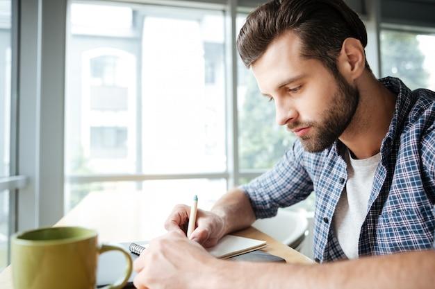 Красивый мужчина в офисе коворкинг во время написания заметок
