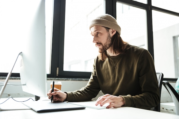 컴퓨터를 사용 하여 사무실에서 잘 생긴 남자입니다. 옆으로 찾고 있습니다.