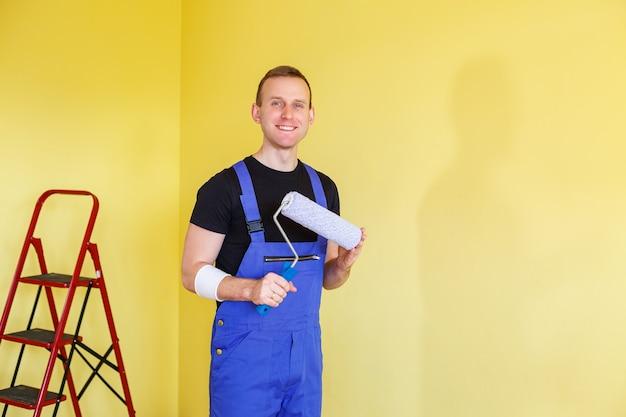 オーバーオールのハンサムな男はペイントローラーを保持します。アパートの部屋の改修のためのツールアクセサリー。リノベーションのコンセプト