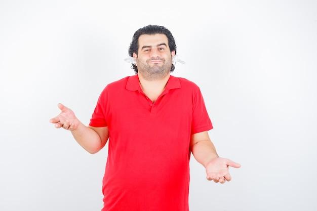 無力なジェスチャーを示し、耳にナプキンを持って立って、困惑しているように見える赤いtシャツのハンサムな男、正面図。