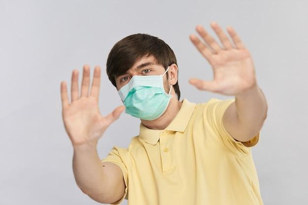 회색에 고립 된 코로나 바이러스 동안 사회적 접촉을 피하기 위해 정지 신호를 보여주는 호흡기 멸균 마스크에 잘 생긴 남자