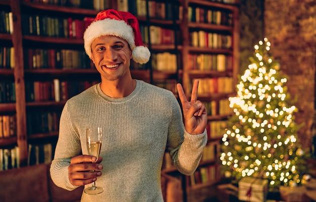 シャンパングラスとサンタの帽子をかぶったハンサムな男。贈り物とクリスマスツリーの背景に。明けましておめでとうございます!