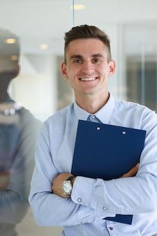 Красивый мужчина в рубашке и папке стоит в офисе