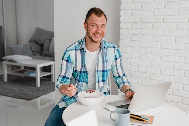 Красивый мужчина в рубашке завтракает дома за столом, работая онлайн на ноутбуке из дома