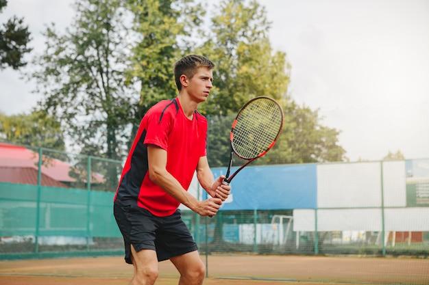 Красивый человек в рубашке держа теннисную ракетку и смотря сконцентрированный пока стоящ на теннисном корте