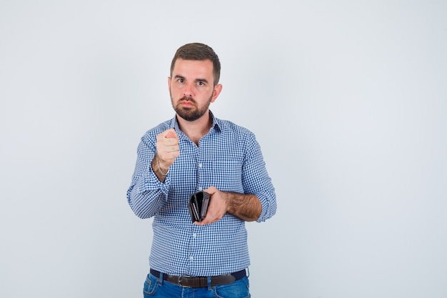 シャツを着たハンサムな男、財布を持っているジーンズ、イチジクのジェスチャーを示し、真剣に見える、正面図。