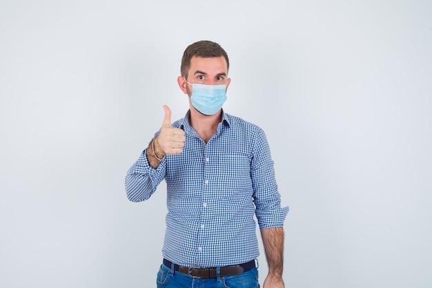 シャツ、ジーンズ、親指を立てて真剣に見えるマスク、正面図のハンサムな男。