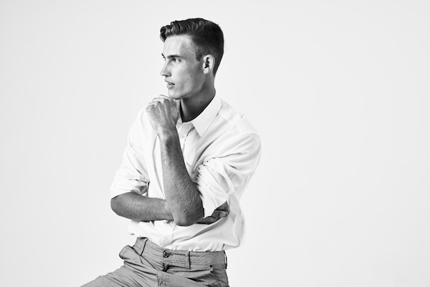 Красивый мужчина в рубашке, сидя на стуле моды элегантный стиль светлом фоне