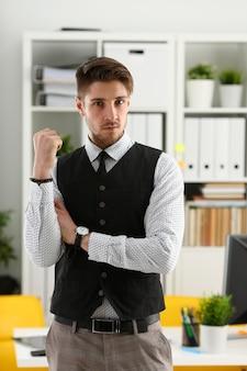 スーツとネクタイのハンサムな男が胸に交差するカメラの手を見てオフィスに立つ