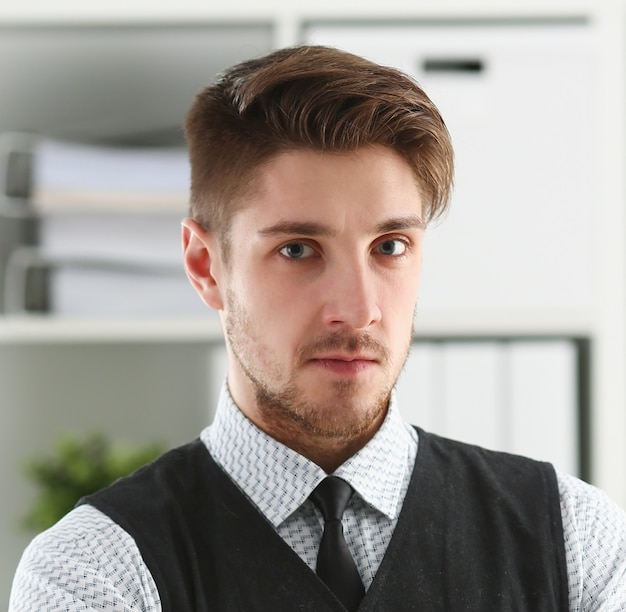 スーツとネクタイのハンサムな男がオフィスに立つ