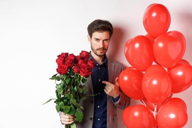 흰색 배경 위에 하트 풍선 근처에 서있는 장미 꽃다발을 가리키는 낭만적 인 발렌타인 데이 날짜에 소송에서 잘 생긴 남자.
