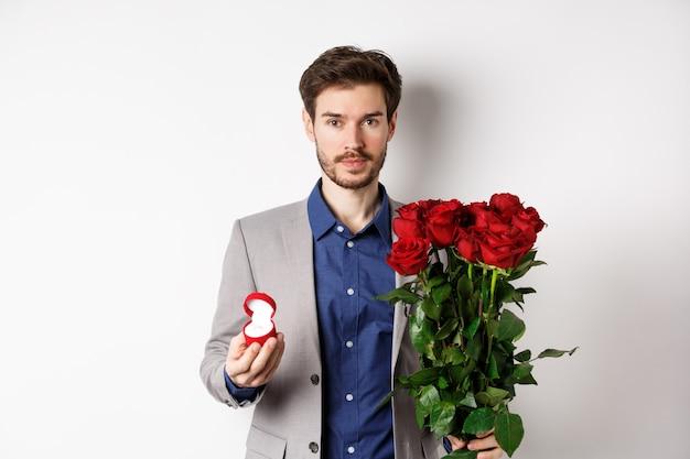 赤いバラの花と婚約リンを箱に入れて立って、ロマンチックな驚き、白い背景を作る、提案をしようとしているスーツのハンサムな男。