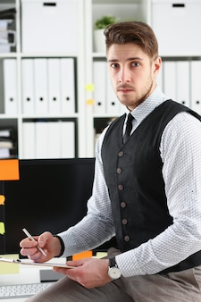 Красивый мужчина в костюме держит в руках серебряную ручку и блокнот