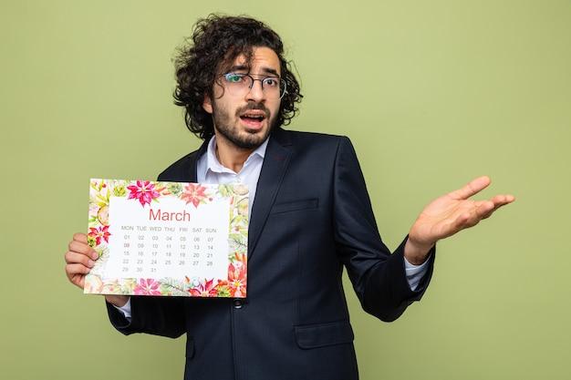Красивый мужчина в костюме держит бумажный календарь на месяц марта, глядя в сторону, недовольно поднимая руку, празднуя международный женский день 8 марта, стоя на зеленом фоне