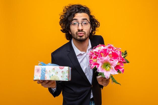 현재와 꽃의 꽃다발을 들고 양복을 입은 잘 생긴 남자가 행복하고 긍정적 인 입술을 유지하는 것처럼 국제 여성의 날 3 월 8 일을 축하합니다.