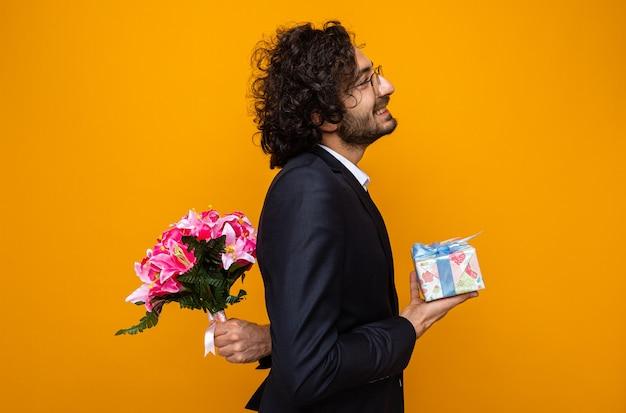 Красивый мужчина в костюме, держащий подарок, прячет букет цветов за спиной, собирается отпраздновать международный женский день 8 марта, стоя на оранжевом фоне