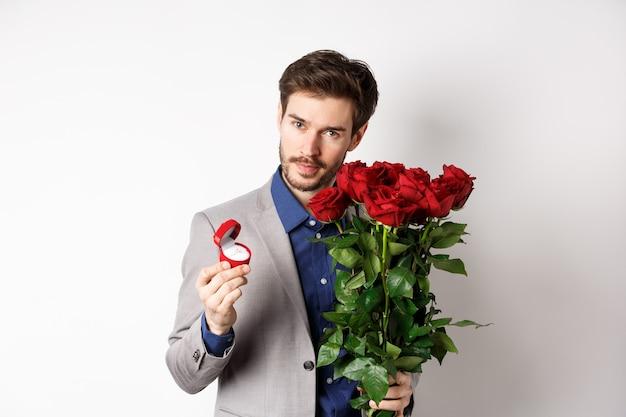 スーツを着たハンサムな男、婚約指輪を示し、カメラをロマンチックに見て、白い背景の上に赤いバラで立っています。バレンタインデーと愛のコンセプト。