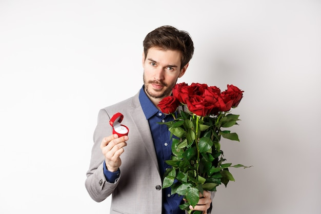 Красивый мужчина в костюме, показывая обручальное кольцо и романтично глядя в камеру, стоя с красными розами на белом фоне. день святого валентина и концепция любви.