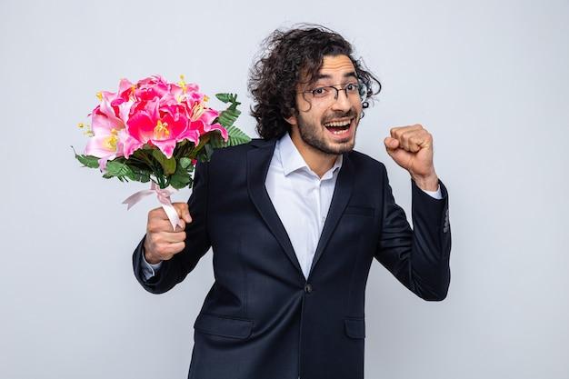 Красивый мужчина в костюме с букетом цветов выглядит счастливым и взволнованным, сжимая кулак