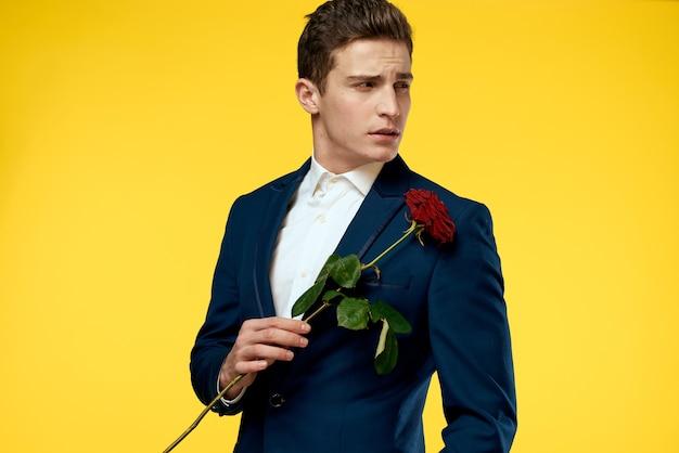 Красивый мужчина в костюме с розой романтика прощай желтая стена.