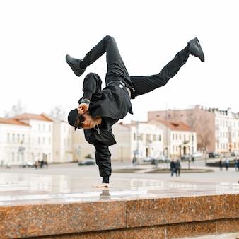 Красивый мужчина в солнечных очках и современной черной одежде танцует в городе.