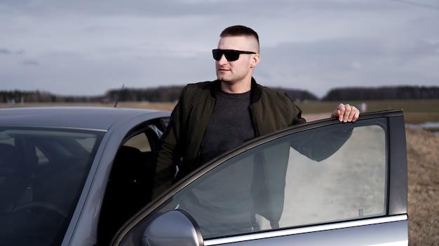 車の近くのサングラスでハンサムな男