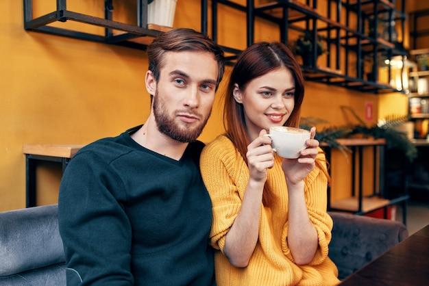 Красивый мужчина в свитере и женщина с чашкой кофе, свидание, ресторан, кафе