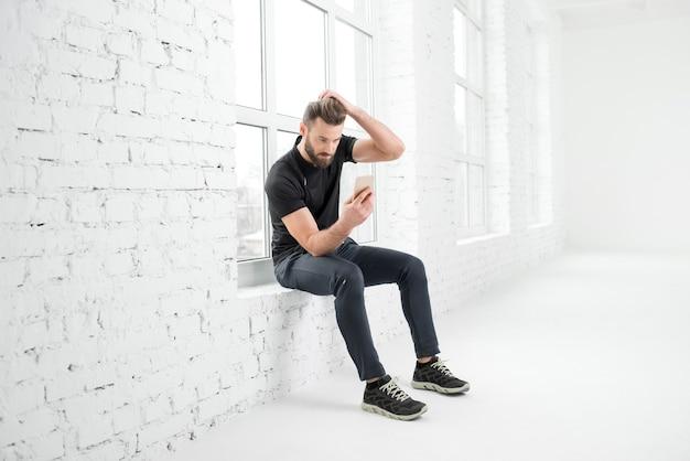 흰색 체육관 내부 창문에 전화기를 들고 앉아 있는 검은색 운동복을 입은 잘생긴 남자