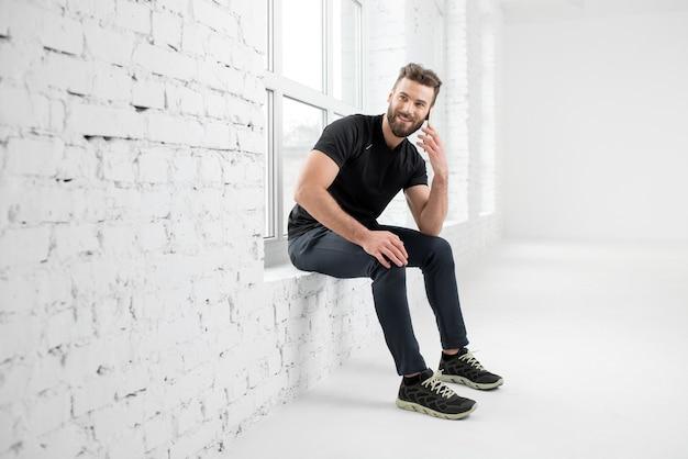 검은색 운동복을 입은 잘생긴 남자가 흰색 체육관 내부에 있는 창에 앉아 전화로 이야기하고 있다