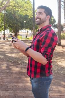 ドローンを操縦する広場のハンサムな男。ドローンで撮影しているリモコンを持つ少年。垂直
