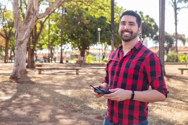 ドローンを操縦する広場のハンサムな男。ドローンで撮影しているリモコンを持つ少年。
