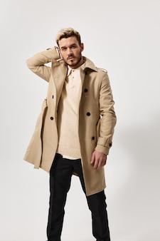 ズボンのボタンを外したセーター コートと頭の後ろに手を着たハンサムな男