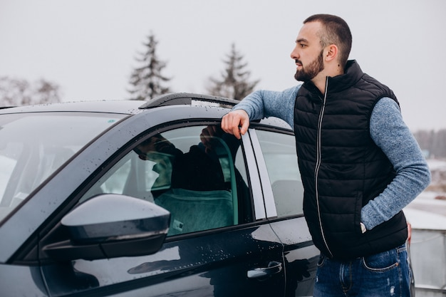 Красивый мужчина в теплой куртке, стоящий на машине, покрытой снегом