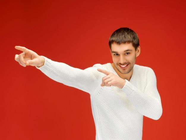 彼の指を指している暖かいセーターのハンサムな男。