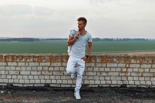 Красивый мужчина в белой одежде стоит у кирпичной стены на крыше.