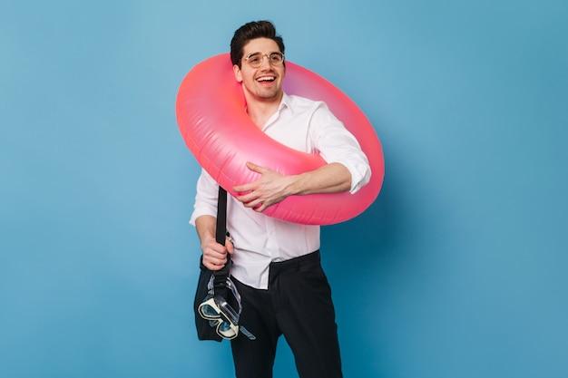 흰 셔츠와 검은 색 바지에 잘 생긴 남자는 푸른 공간에 대해 웃고있다. 직원은 휴가를 시작할 때 기뻐하며 고무 링과 수영 마스크를 들고 있습니다.