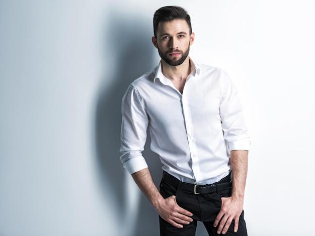 白いシャツと黒いズボンのハンサムな男-ファッションの髪型で魅力的な男をポーズします。短いあごひげを持つ自信のある男。茶色の髪の大人のスタイリッシュな男の子。