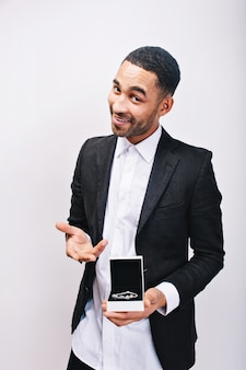 Красивый мужчина в белой рубашке и элегантной черной куртке, держа в руках ювелирный подарок и улыбаясь. праздники, подарок, хорошее настроение, украшения, настоящие положительные эмоции.
