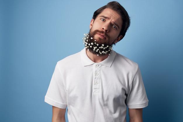 ひげの装飾の青い背景の白いシャツの花のハンサムな男