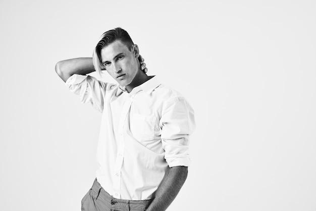 白いシャツを着たハンサムな男は彼の頭の後ろに手を握ってエレガントなライフスタイル