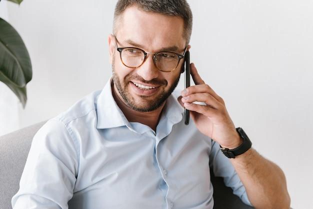 笑みを浮かべて、オフィスで働いている間、ビジネスについて黒のスマートフォンで話している白いシャツでハンサムな男