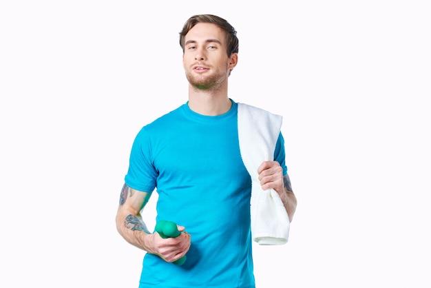 腕のトレーニングクロップドビューに白いtシャツの入れ墨のハンサムな男