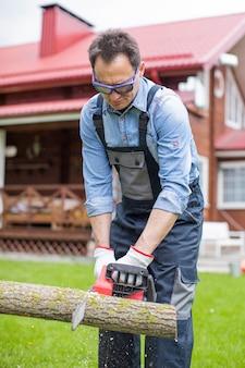 家の近くの電気のこぎりで制服木を挽く作業でハンサムな男