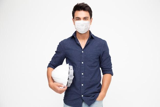 白いヘルメットを保持し、白い壁に分離されたウイルスcovid-19を防ぐための防護マスクを身に着けているハンサムな男産業エンジニア