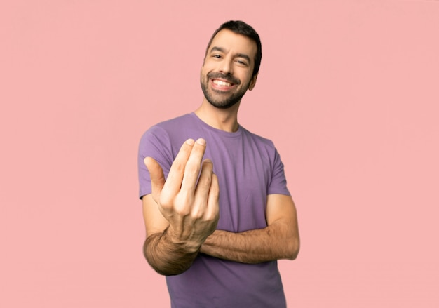 Handsome man inviting to come with hand. happy that you came on isolated pink background