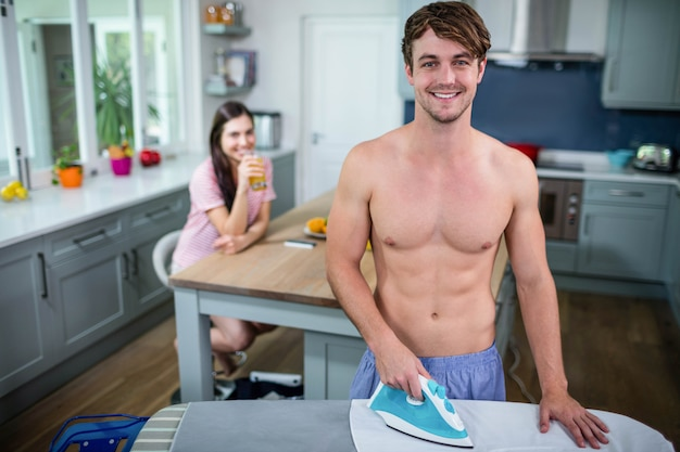 Handsome man ironing in the kitchen while woman is looking at him