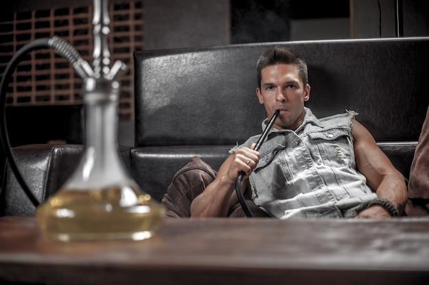 ハンサムな男がナイトクラブで煙を吹いています。