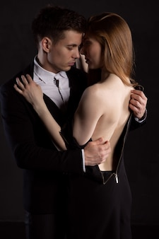 The handsome man is concentrating on removing the dress from the girl, who gently embraces him