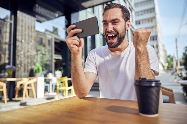 잘 생긴 남자는 카페에서 커피와 함께 테이블에 앉아 스마트 폰을 찾고 행복합니다