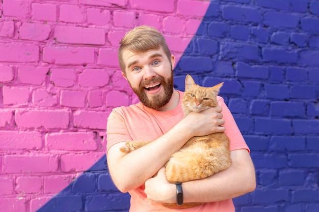 잘생긴 남자가 야외에서 귀여운 고양이를 안고 껴안고 있습니다.
